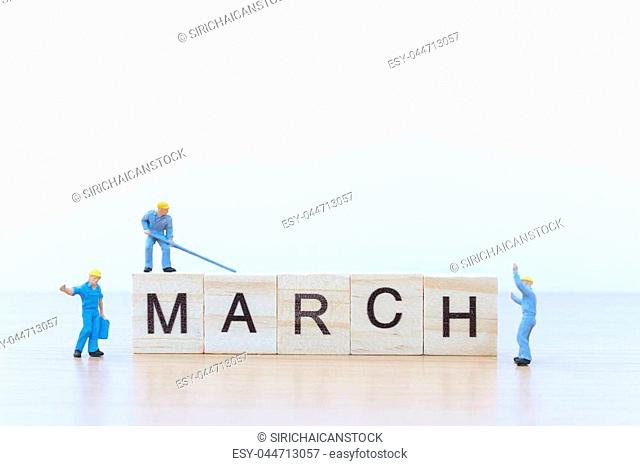 March words with Miniature people worker on wooden floor