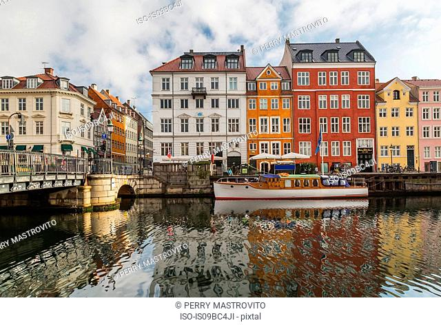 Moored boat and bridge with colourful 17th century town houses on Nyhavn canal, Copenhagen, Denmark