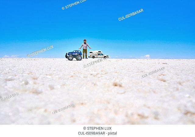 False perspective image of boy and toy truck on salt flats, standing taller than recreational vehicle in background, Salar de Uyuni, Uyuni, Oruro, Bolivia