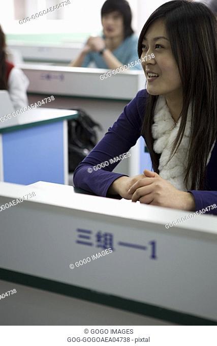 Student smiling at her desk