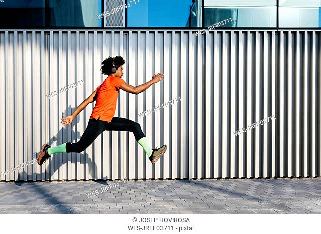 Young man jumping in the city, metallic wall in the background