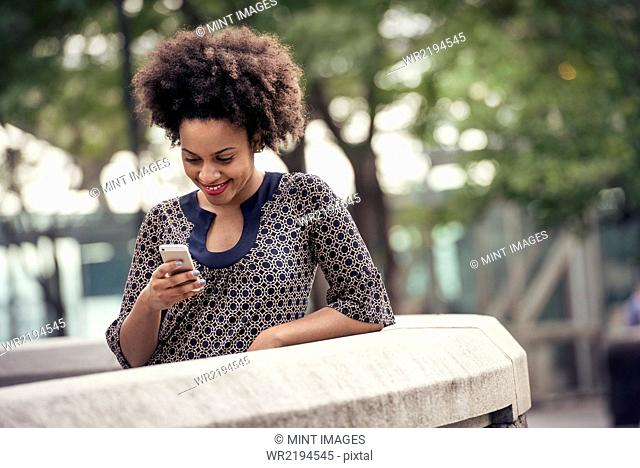 A woman in a park checking her cell phone