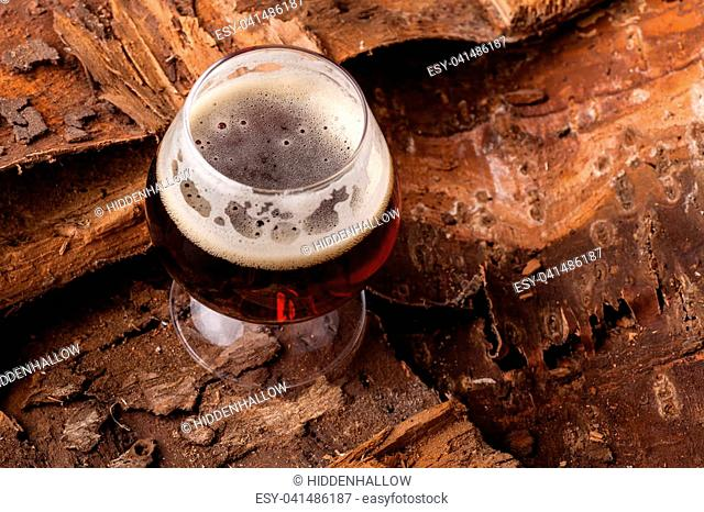 Snifter glass of dark beer standing on a pile of dry wood bark