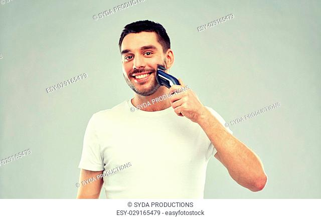 beauty, grooming and people concept - smiling young man shaving beard with trimmer or electric shaver over gray background