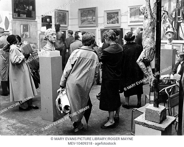 Scene at the opening of an art exhibition by The London Group of artists, with the walls full of paintings, two portrait busts on plinths and a crucifixion