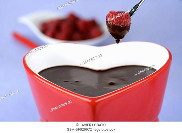 Heart-shaped chocolate fondue dipping a raspberry