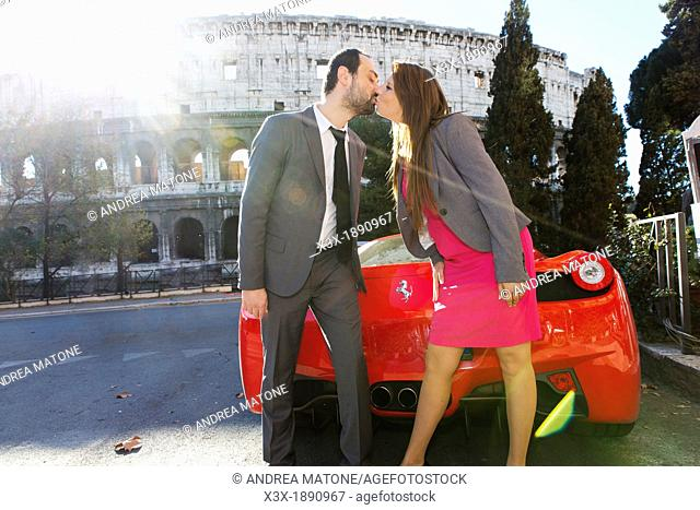 Couple kissing by a red ferrari in front of the Roman Colosseum in Rome Italy