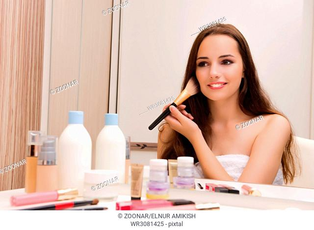 Woman doing make-up at home preparing for party