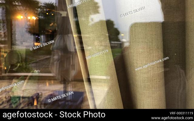 Woman Looking Through a Window with Curtain and Reflection in Switzerland