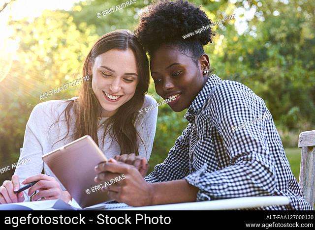 Smiling young friends using digital tablet while studying in park, Orgeval