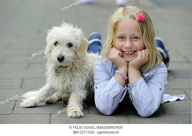 Girl with a mixed breed puppy lying on a pavement