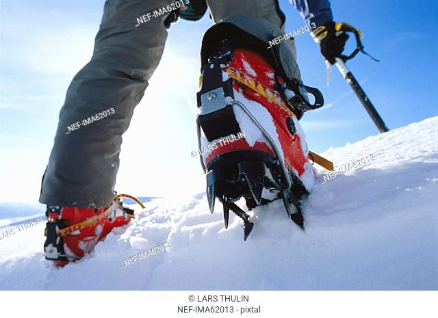 Low section of person wearing crampons