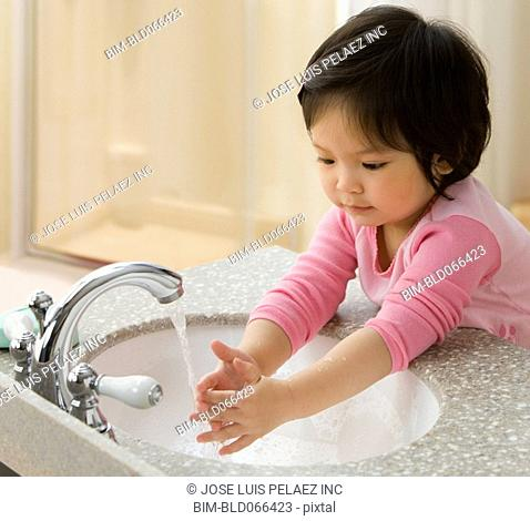 Mixed race girl washing her hands