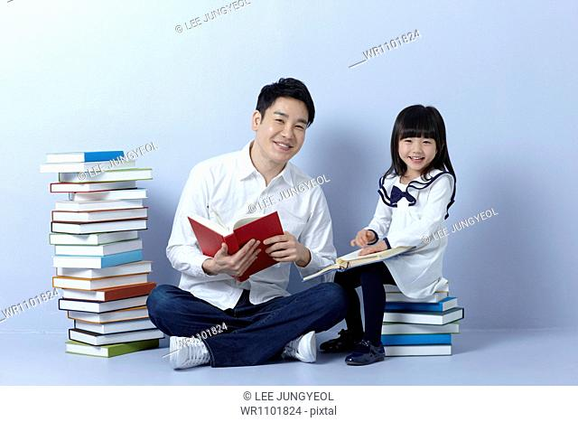 a father reading books with his daughter
