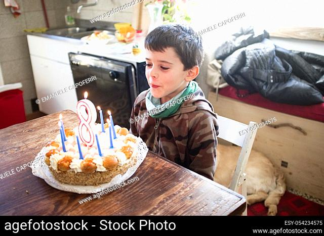 child turns eight years and blows out the candles of the cake