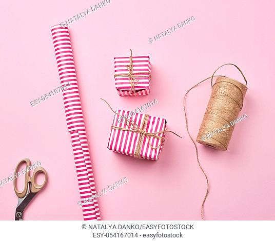 skein with a brown rope, roll with holiday wrapping paper, scissors and two gifts, top view, DIY crafts