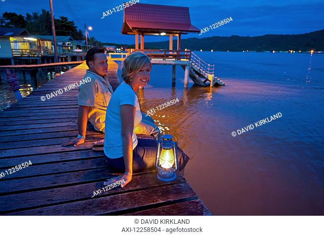 Tourists relaxing at dusk in a small village; Brunei