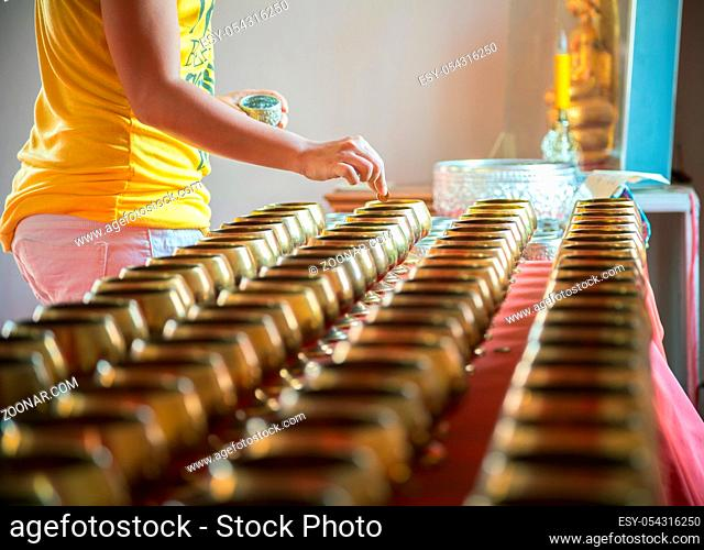 young adult woman donate her money in temple