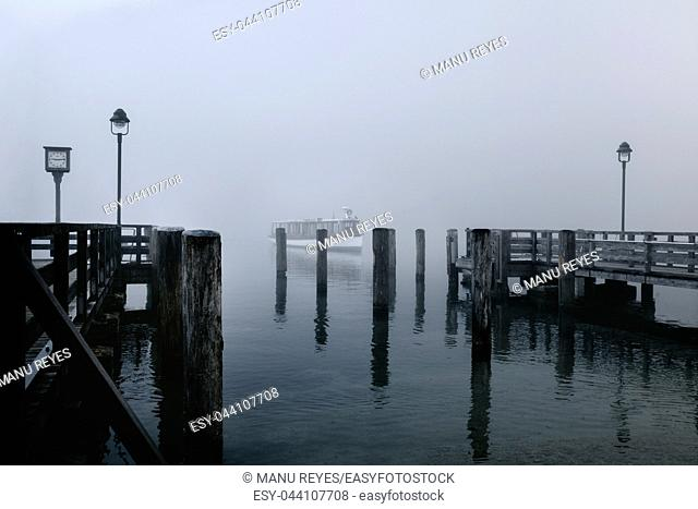 Views of the wooden pier in the mist and a lone boat on the Konigsee lake of Germany with wooden posts that get lost in the fog
