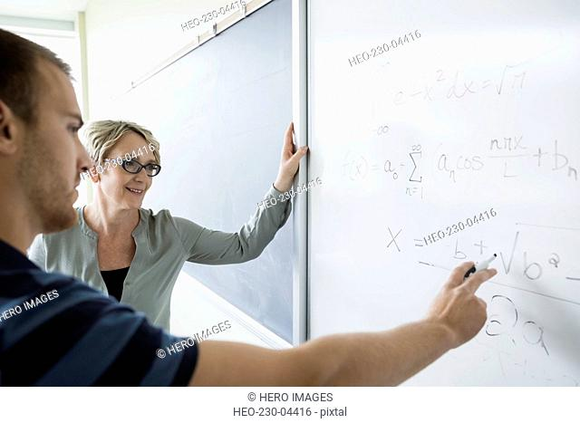 Trigonometry professor and college student solving equation whiteboard