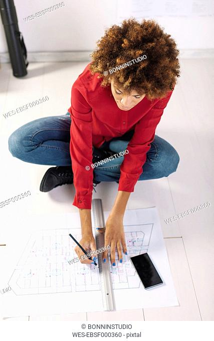 Young female architect working on the floor of her office