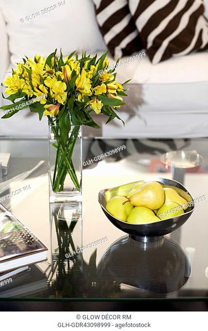 Flower vase and a bowl of artificial pears on a table