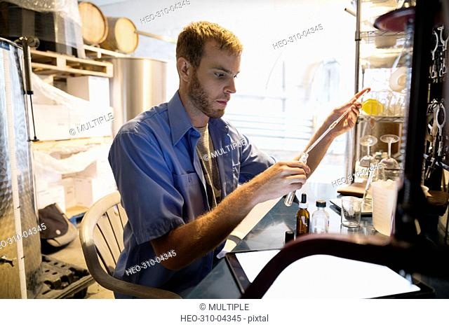 Vintner with pipette and test tube checking wine