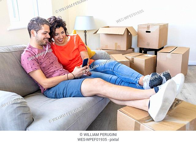 Happy couple using cell phone on couch in new home
