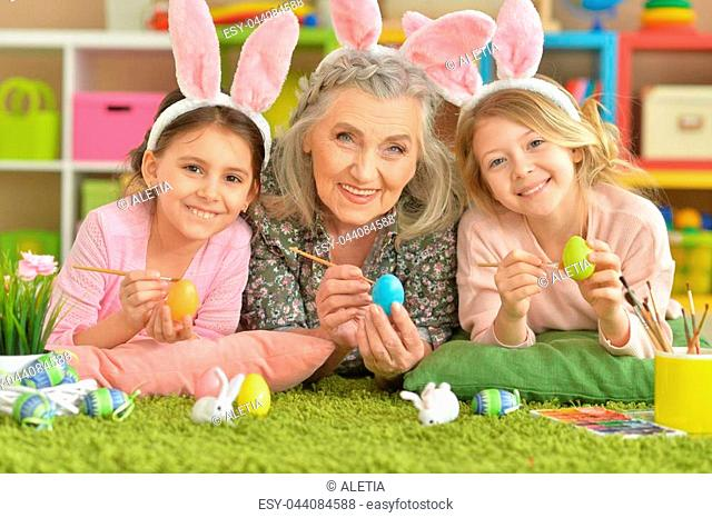 Portrait of a grandmother and two granddaughters paint Easter eggs
