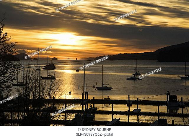 Silhouetted boats on sea, Salt Spring Island, British Columbia, Canada
