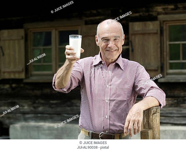 Senior man holding glass of milk