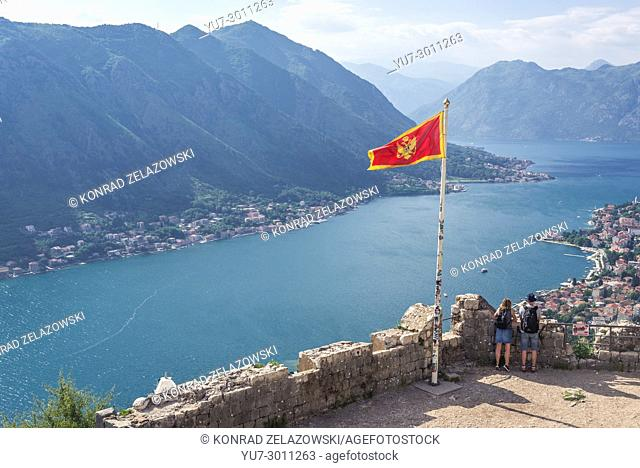 Montenegrin flag on the top of Saint John Fortress ruins above Kotor coastal city, located in Bay of Kotor of Adriatic Sea, Montenegro