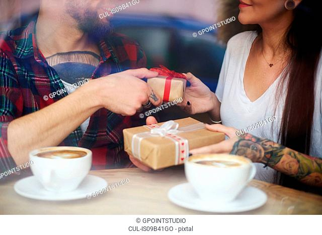 View through window of couple in coffee shop exchanging gifts