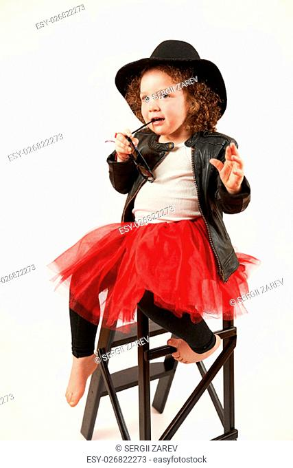 Little girl with black hat and sunglasses sitting and thinking