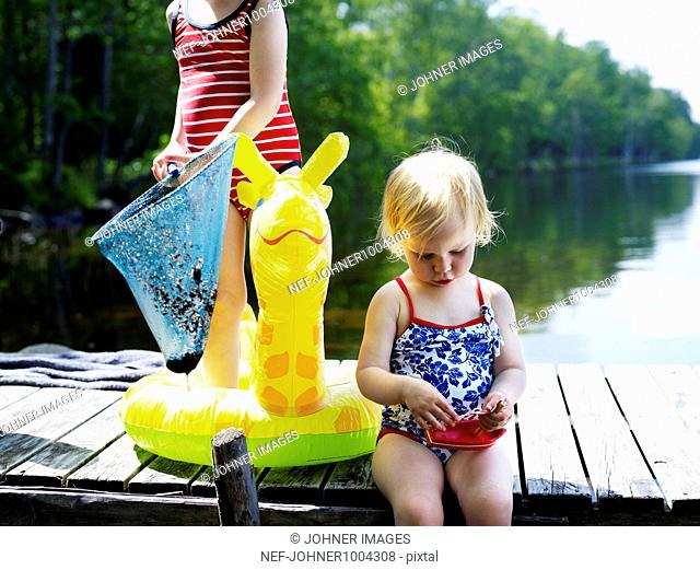 Scandinavia, Sweden, Two girls (2-5) on pier holding toy and fishing net