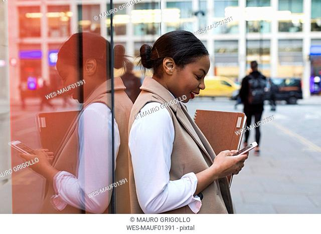 Smiling businesswoman leaning against glass pane using cell phone