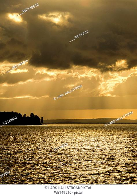 Lake at twilight, silhouette of forest and dramatic sky with sunbeams. Dark and moody nature background