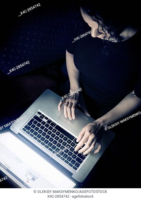 Woman using a laptop computer at home, overhead view, Facebook login page on display
