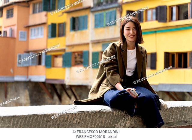 Italy, Florence, smiling young woman resting on a wall in the city