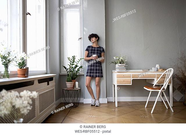 Young woman with coffee mug looking through window at home