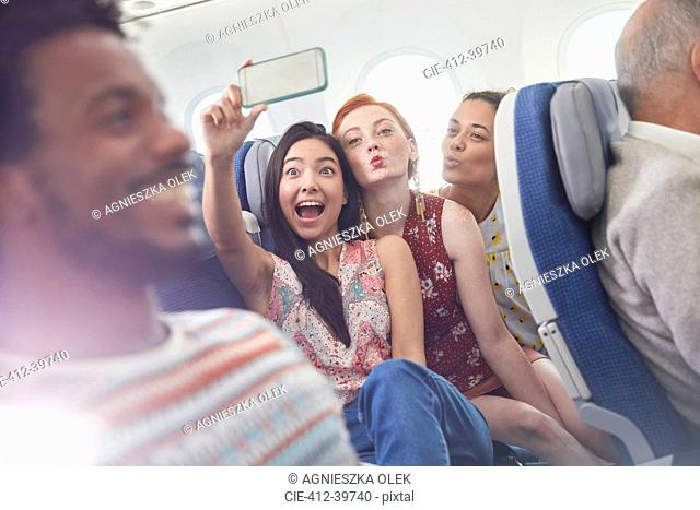 Playful young friends with camera phone taking selfie on airplane