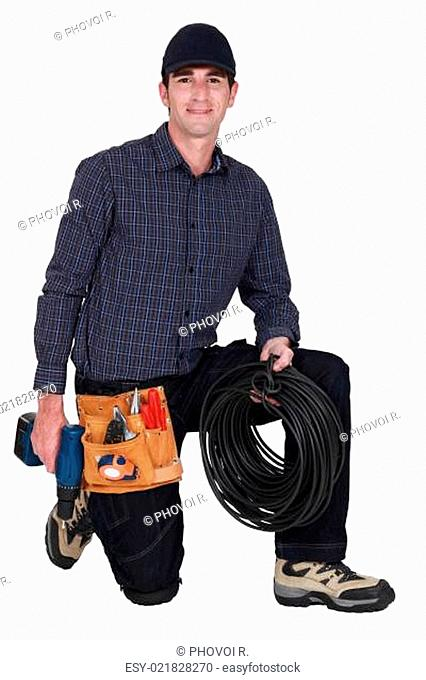 Electrician kneeling with drill and cable