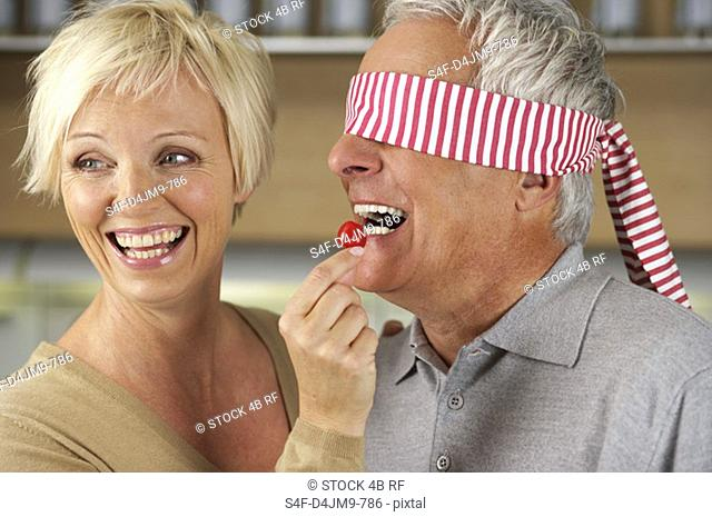 Blonde woman letting a man, who's eyes are covered, taste a red pepper, close-up