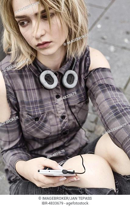Fashionably dressed young woman, teenager, sitting depressed on the floor with smartphone in her hand, North Rhine-Westphalia, Germany, Europe