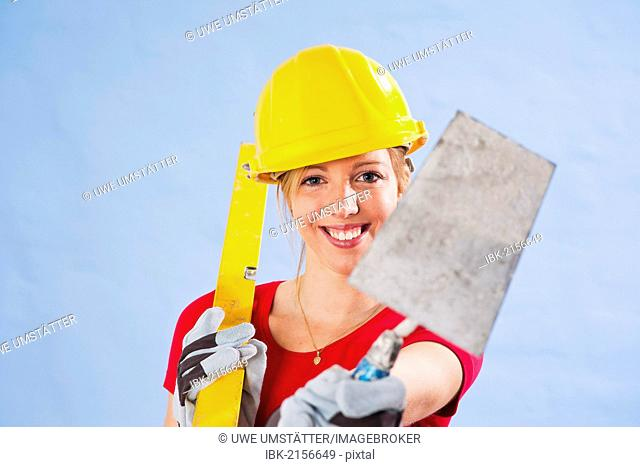 Young woman wearing a yellow safety helmet holding a spirit level and trowel in her hand