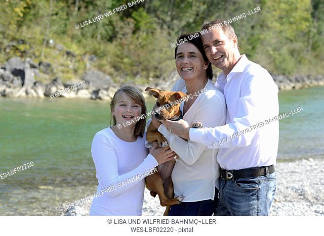 Happy family with a dog at the river Isar, Upper bavaria, Germany