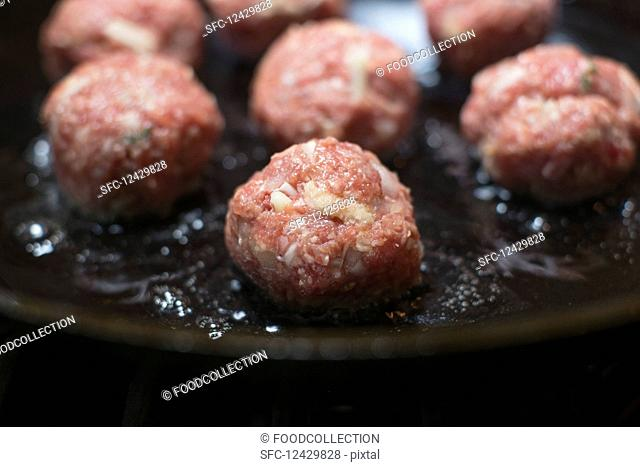 Raw meatballs being fried in a pan