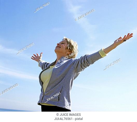 Portrait of a middle aged woman with her arms spread against blue sky