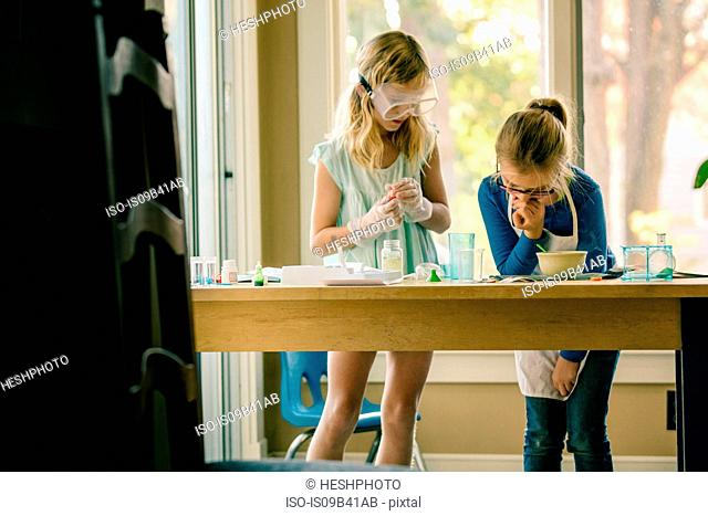 Two girls doing science experiment, reading chemistry set instructions