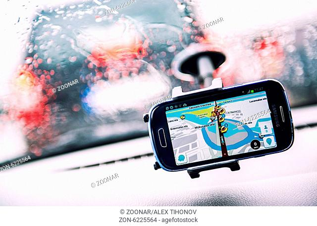 Smart phone with a Waze GPS navigator on the screen. Waze is one of the world's largest community-based traffic and navigation apps